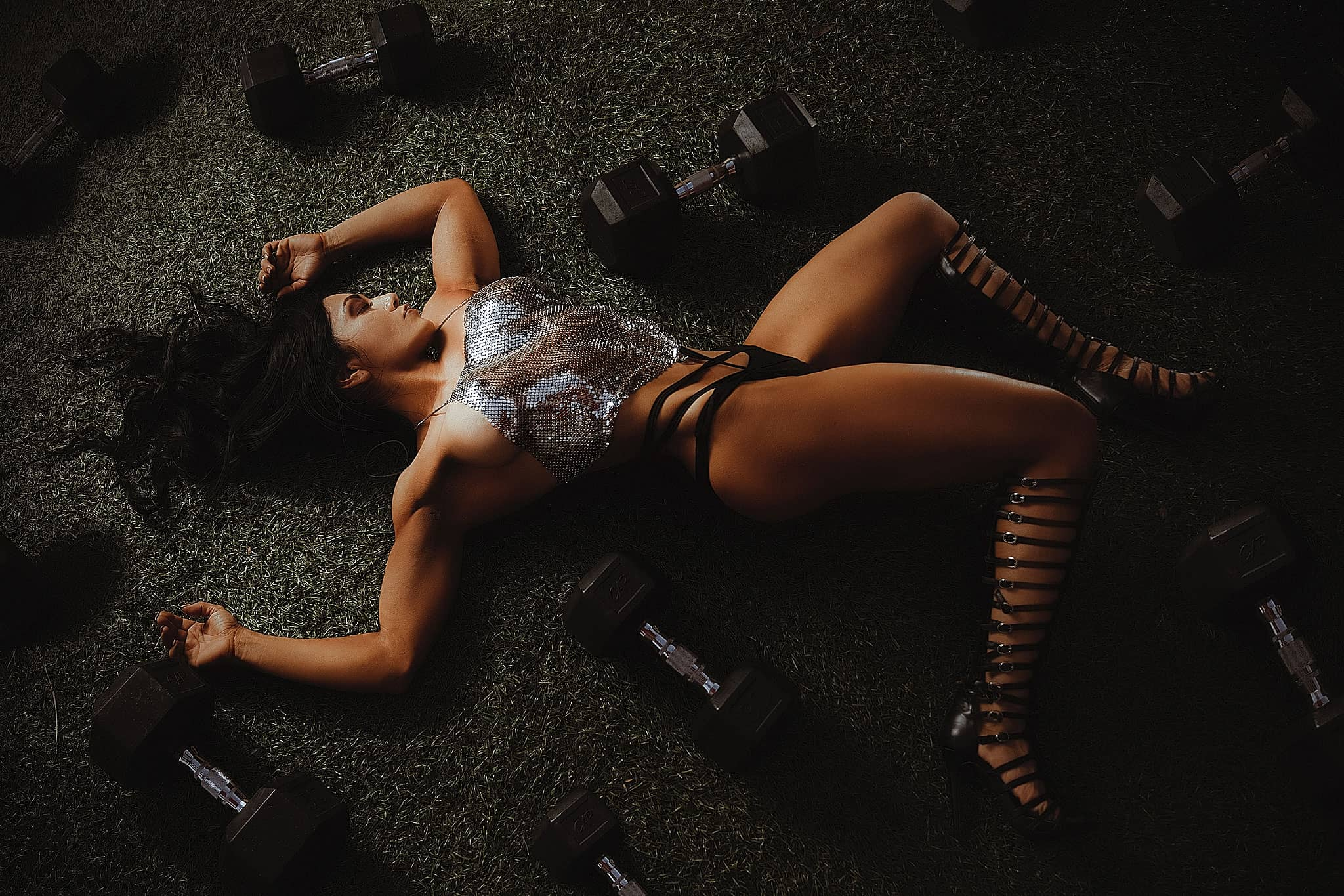 Header Commercial fitness-model-in-reflective-dress-relaxing-on-the-gym-floor-with--dumbbells